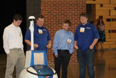 Pictured are BSC robotics team student members (dark blue shirts) are detailing the capabilities of their intelligent ground vehicle to members of the Ridgeview High School robotics team.