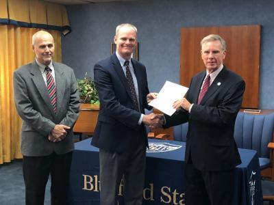 Diversified Energy Corporation President/CEO Paul Nester (center) presents a gift deed to Bluefield State College President Robin Capehart (right), granting and releasing to BSC two parcels of real estate adjacent to new student housing now under construction on BSC's campus.  BSC alumnus Jim Shockley (left), Company Chief Operating Officer/VP, also took part in the program.